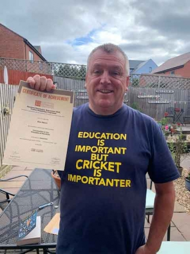 Electrium Sales, Alan Slavin, says it all with his top! Here he is at home with his Distinction certificate for his first module Introduction to the Principles of Electricity.