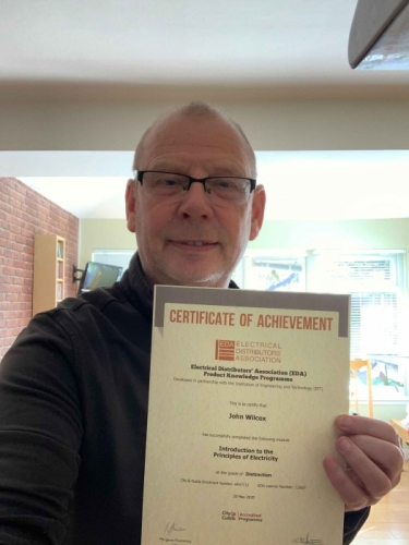John Wilcox of Electrium Sales, with his certificate for Introduction to the Principles of Electricity.