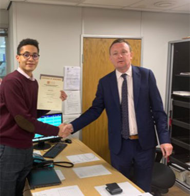 Ashley Waters (l) of Edmundson Electrical Blackfriars receives his Distinction certificate from manager Paul Conneely. (March 2019)