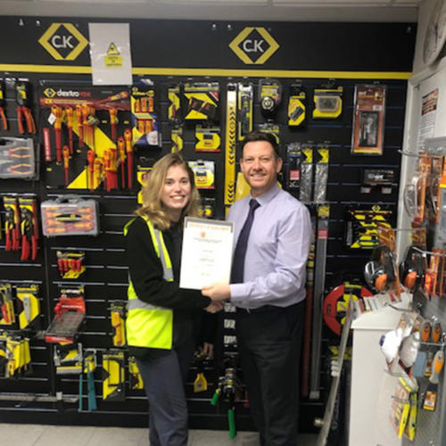 Harriet Eagle (l) Edmundson Electrical, King's Lynn, receiving her Distinction certificate from manager David Grimes (r)